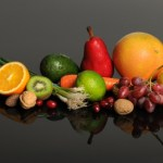 A selection of fruits and vegetables on a reflective black background.