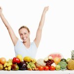 A happy women with her arms raised behind a selection of healthy foods.
