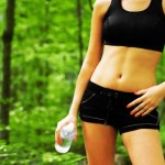 A woman with toned abs standing in a forest with a bottle of water.