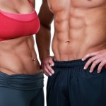 A close up shot of a couple with toned abdominal muscles.