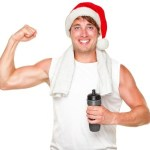A man flexing his right bicep while holding a water bottle and wearing a Christmas hat.