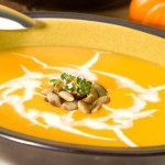 A bowl of creamy pumpkin soup topped with pumpkin seeds.