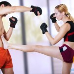 A man and woman kick boxing.