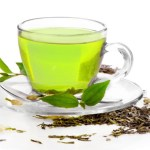A g;ass cup of green tea surrounded by green tea leaves.