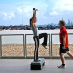 A personal trainer with a client training outside.