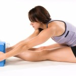 A woman stretching with a yoga block.