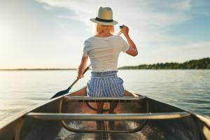 Young woman canoeing on a sunny afternoon in summer