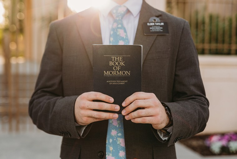 LDS missionary photoshoot in front of the gilbert arizona temple holding book of mormon