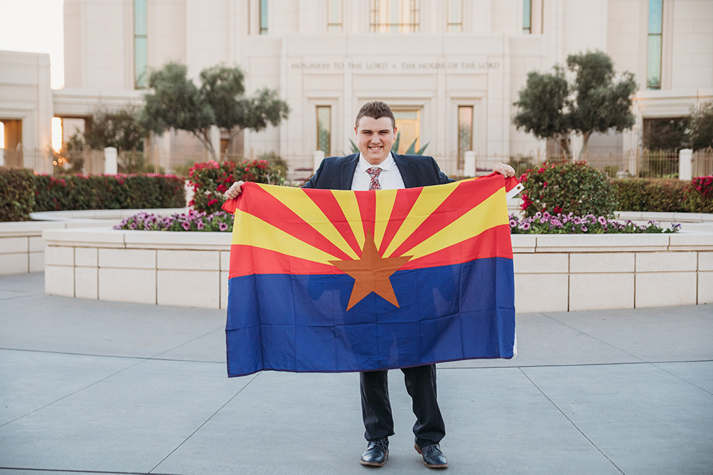 LDS missionary photoshoot in front of the gilbert arizona temple holding arizona flag