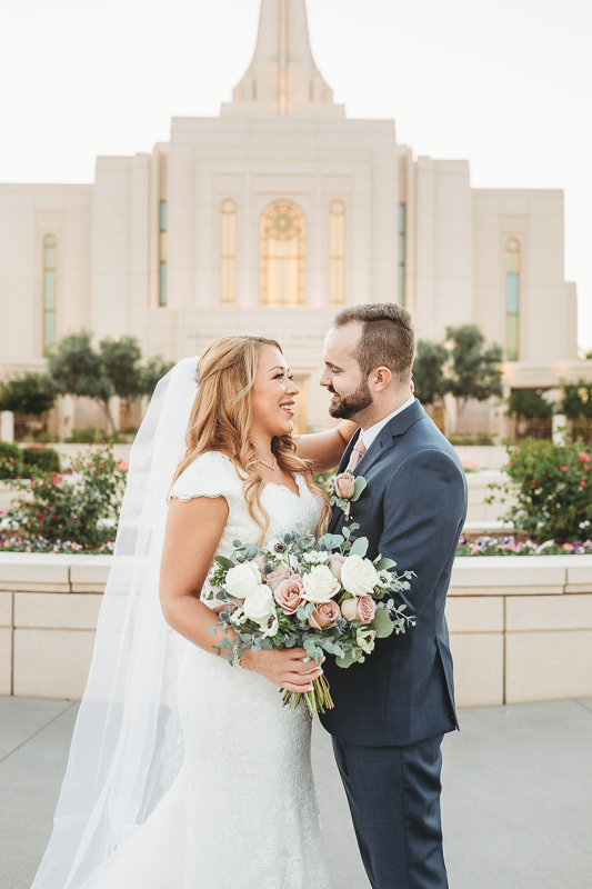wedding photos of bride and groom hugging in front of the gilbert arizona temple