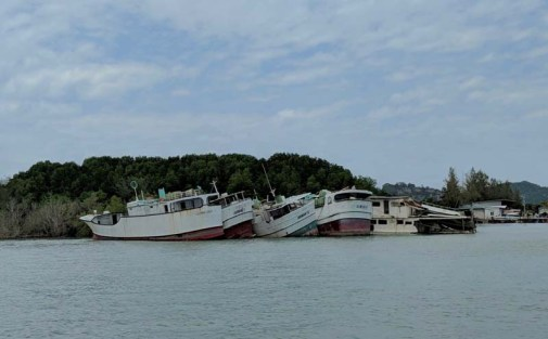 On approach to the pier in Phuket Town - harbor still supporting dilapidated vessels