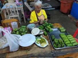 An elder creating treats with banana leaves