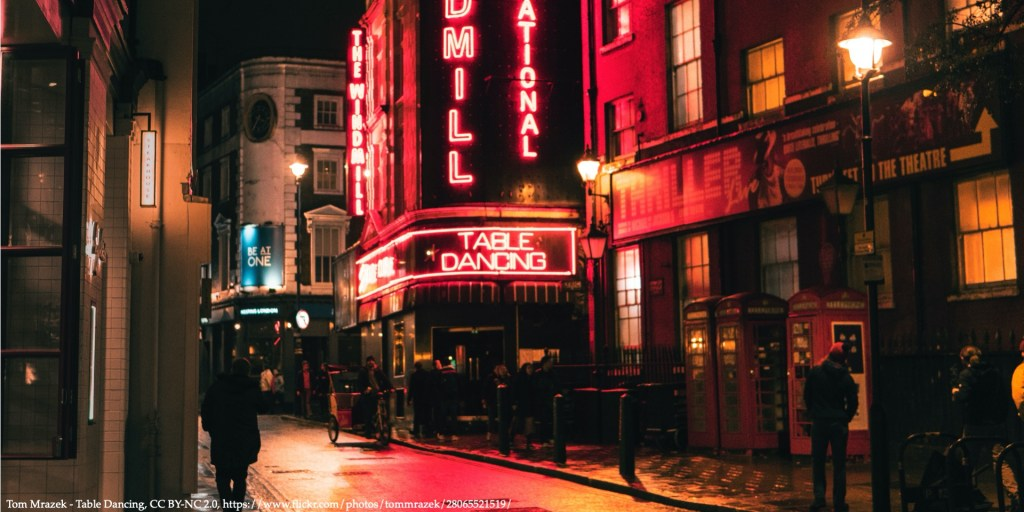 An image of red light street with signs of striptease club representing human trafficking and prostitution legislation