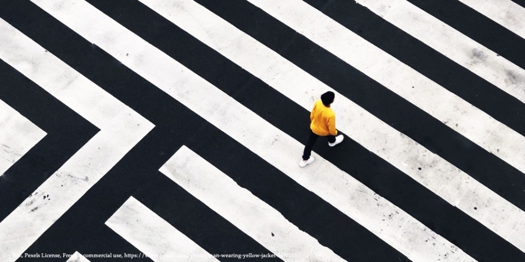 Image with black and white stripes and person in yellow jacket walking representing conference on rethinking gender