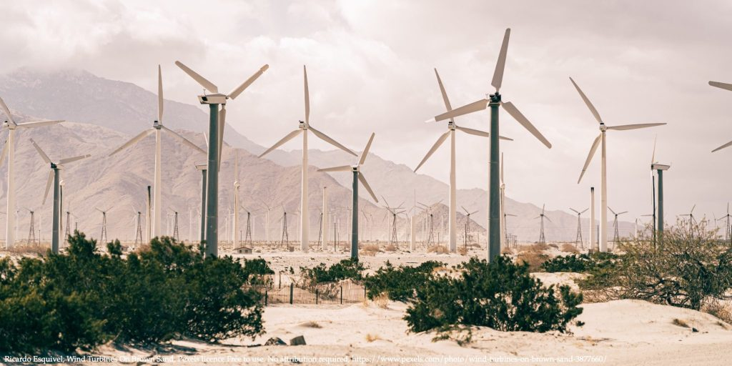 Wind turbines in a sunny desert representing energy storage
