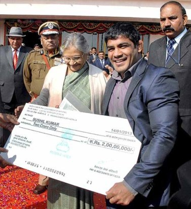 Sushil Kumar receiving a cheque of Rs. 2 crores from former CM of Delhi, Sheila Dixit