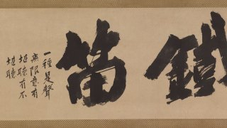 detail from a Japanese scroll - calligraphy in black ink on a tan paper background