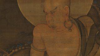bald man with big hoop earrings and halo