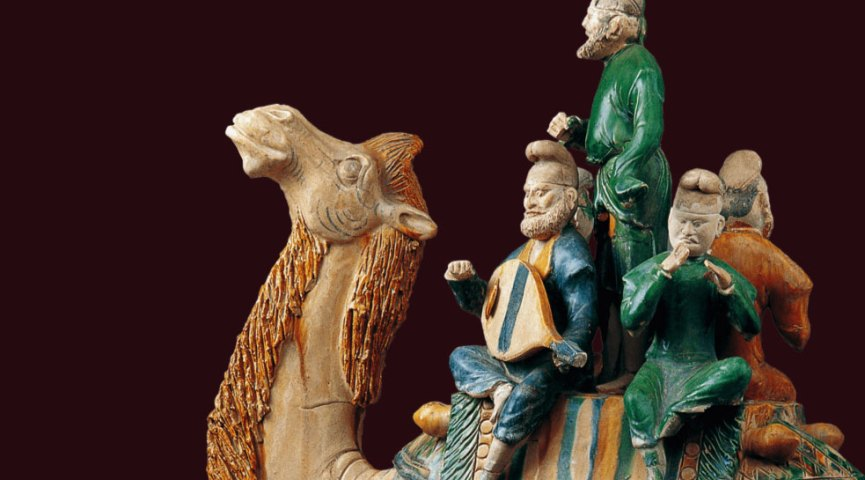 detail from a ceramic sculpture of figures on a camel, in tan and green tones, on a burgundy background