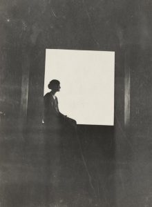 monocrome image of woman sitting in window