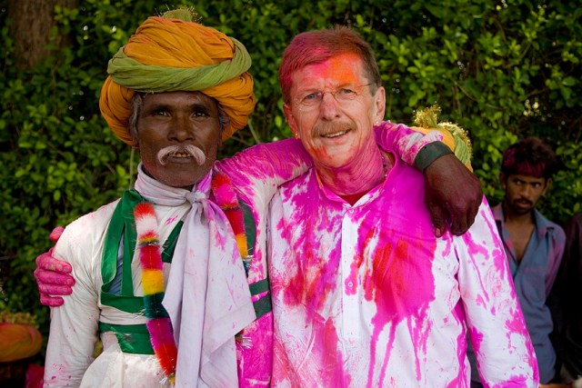 Two men with arms around each other shoulders - one covered in pink dye from Holi.