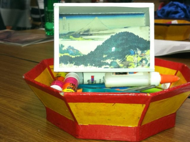 Japanese paper diorama of a landscape, sitting on top of glue sticks in a red and yellow bowl.