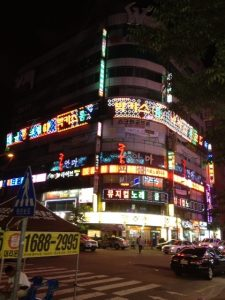 Night image of corner building covered in neon.