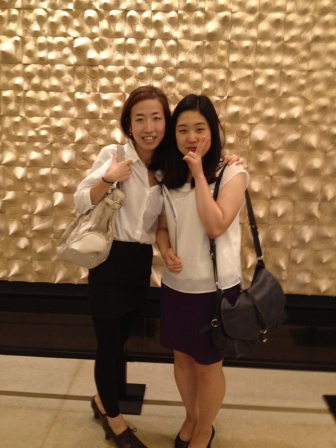 Two women standing in front of gold-white textured wall.