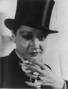 Anna May Wong in top-hat and tuxedo, holding champagne glass right hand.