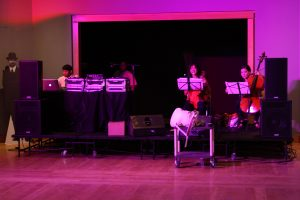 DJ Spooky and musicians Danielle Cho and Jennifer Kim standing behind black table - image washed in pink lighting