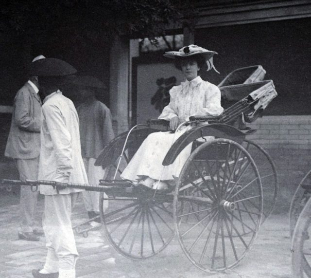 Black and white photo of woman sitting in rickshaw.
