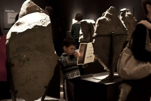 Child looking at brochure while in front of stone exhibition object.