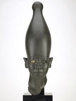 Stone sculpture of a pharaoh's head with one remaining copper inlaid eye.