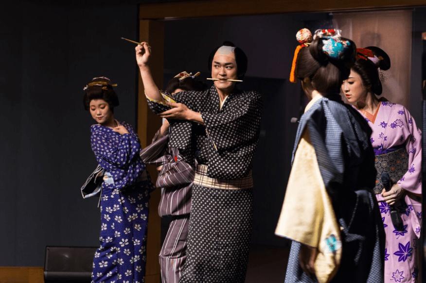 Utamaro pulls back his sleeve while actresses pose around him