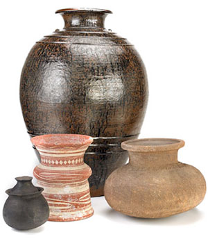 An arrangement of four ceramic vessels of various shapes, sizes, colors, and styles.