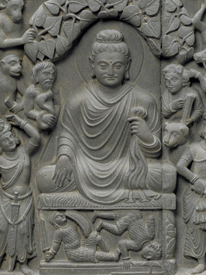 Detail of stone relief of seated Gautama Buddha, surrounded by mountain men, animals, and devas.