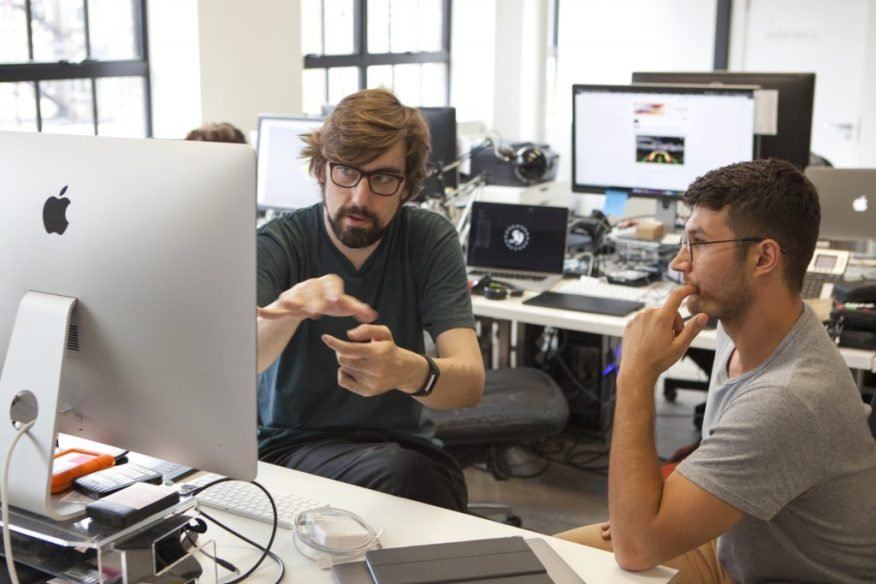 Behind the scenes: in the 59 Productions studio, two men discuss something while seated at a computer