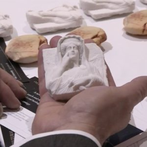 white 3D printed replica held in the palm of a hand