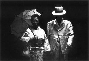 black and white photo of a woman in a kimono holding an umbrella and a man in a suit and hat