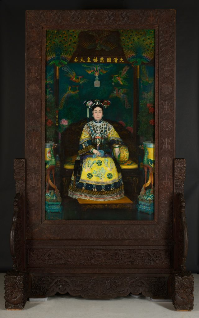 painting of the empress if yellow decorated dress with large headdress and jewelry against a dark green-blue background. The painting is in a large engraved dark wood freestanding frame