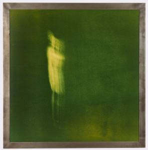 a vaguely humanoid figure, distinguished by a light green hue, floats in a hazy dark green background