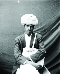 South Asian man with turban sits and holds rectangular object.