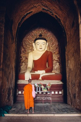 A monk paying homepage to the Buddha statue