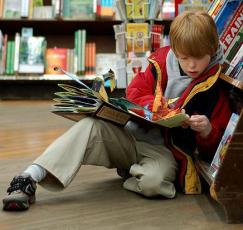 Child_reading_at_Brookline_Booksmith by Mr Absurd from wikimedia commons