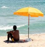 Man_sitting_under_beach_umbrella by Johner common wiki