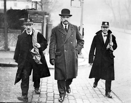 Reginald Bray escorted by two postmen while being 'transported' as a human letter.