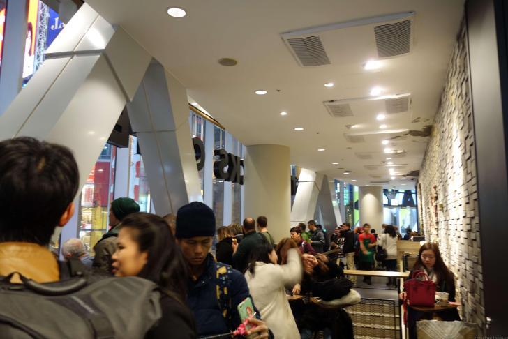 スターバックス2階からスクランブル交差点を眺める外国人観光客