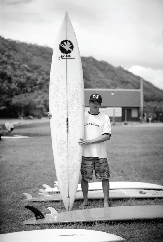 """Eric Arakawa- Ronnie Burns Waimea Gun In the 8th grade, I asked Eric Arakawa if I could borrow a board for Waimea. He let me borrow this board to try out. It was neon yellow in color, thick, with a 9"""" single fin. I rode it for the next two years every day that Waimea broke, and I caught my first-20 footer on it in the 10th grade. Eric saw me walking back home from the session and said, """"I need that board back, it was pretty big out there. This is my friend Ronnie's board."""" I thanked him so much for the time spent with that board, not knowing who he was talking about. A while later I put it together: it was Ronnie Burns' last Waimea gun shaped by Eric himself."""