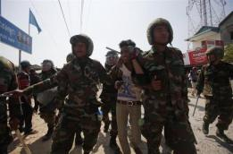Cambodian soldiers escort a worker who had been taking part in a protest after clashes broke out, on the outskirts of Phnom Penh