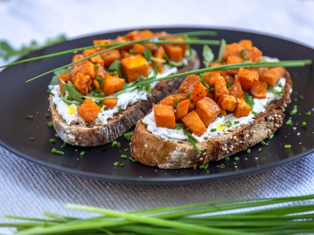 Une recette de tartines au fromage frais, ail et ciboulette avec des petits cubes fondants de patate douce !  Un délice pour l'apéro. Recette végétarienne.